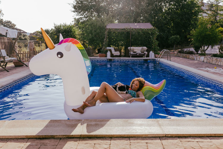 Young woman lying on swimming pool