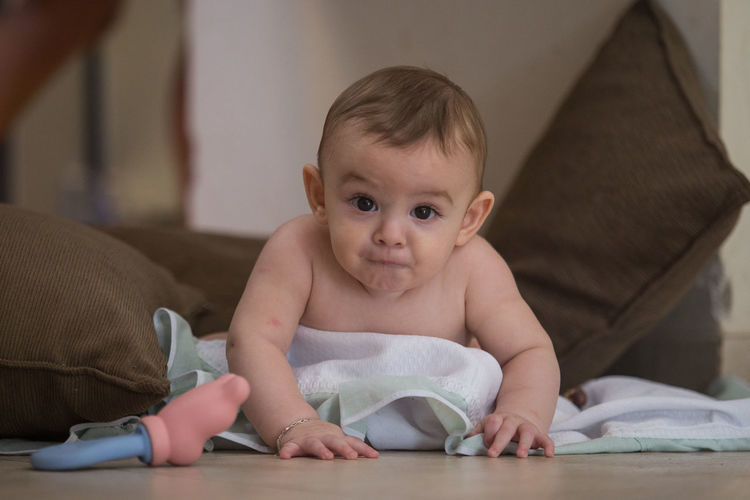 Baby sited on the floor making funny face. Baby Babyboy Babyhood Casual Clothing Childhood Close-up Comfortable Cute Funny Funny Faces Home Innocence Leisure Activity Lifestyles Love Lovely Lying Down Portrait Relaxation Relaxing Resting Sitting Sofa Toddler  Toys
