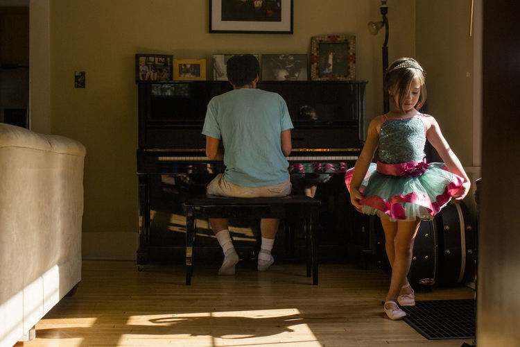 Rear view of girl standing on floor at home