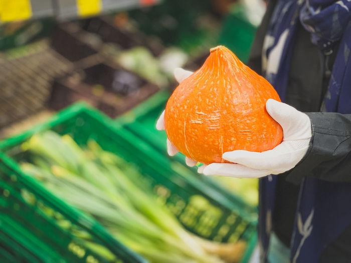 Close-up of man holding orange leaf at store