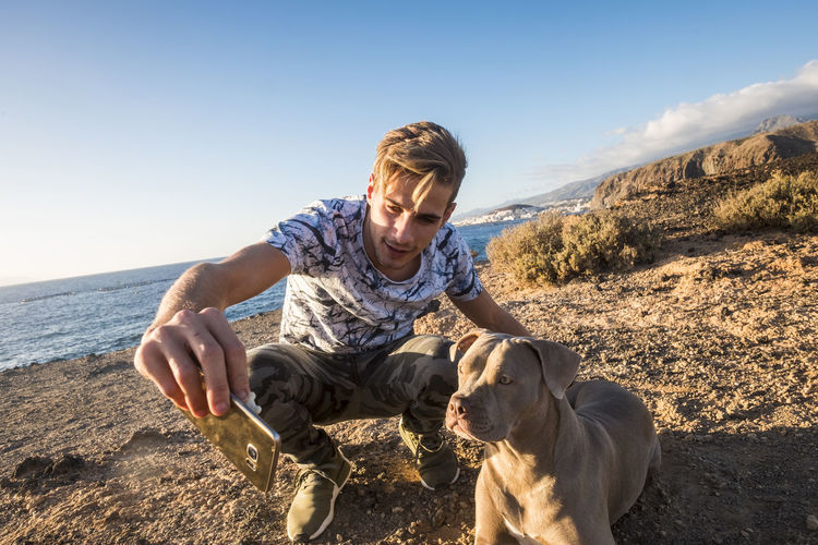 Man With Dog At Beach Against Sky