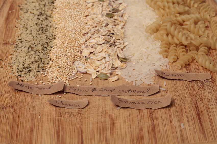 Multiple organic grains, including fusilli, jasmine rice, quinoa, hemp seed, and a mix of grains and seeds oatmeal, on a cutting board on a rustic farm picnic table in summer. Background Close-up Cutting Board Farm Fusilli Grains Hemp Hemp Seeds Jasmine Rice Label No People Oatmeal Organic Pasta Quinoa Rice Texture