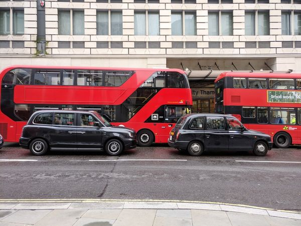 Old & new Blackcabs on side of double decker red London buses Double Decker Bus Blackcab London Day Streetphotography New Old Electric Electric Car Black Taxi Cab Editorial  Cloudy Day Building Exterior Station Rescue Vehicle High Street Street Scene Traffic Bus