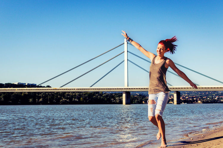 Playful woman having fun on the beach while running with arms outstretched in summer day.
