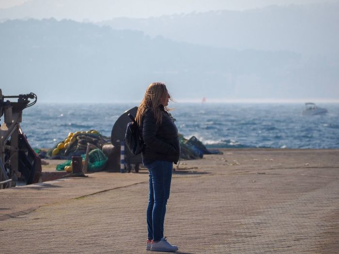 Side view of woman looking at sea while standing on promenade
