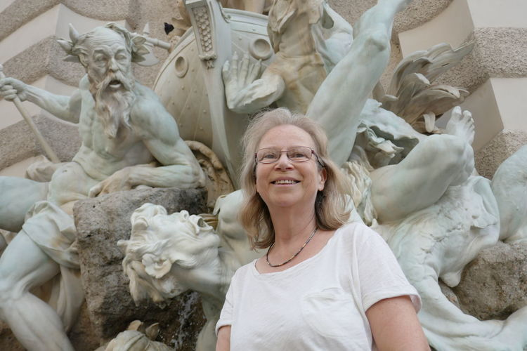 Close-Up Of Smiling Woman Standing Against Statues