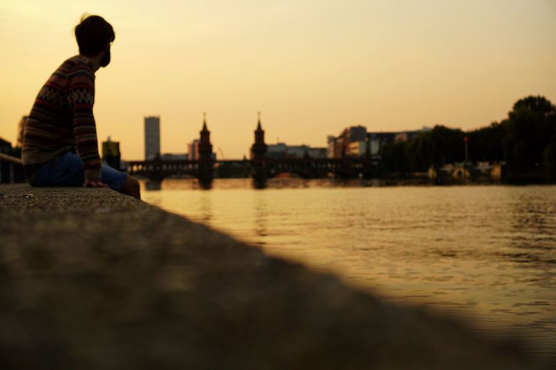 Side View Of Man Sitting At Promenade By Spree River During Sunrise