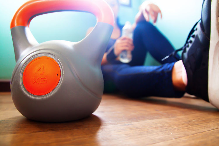 Close-Up Of Kettlebell With Woman Sitting In Background