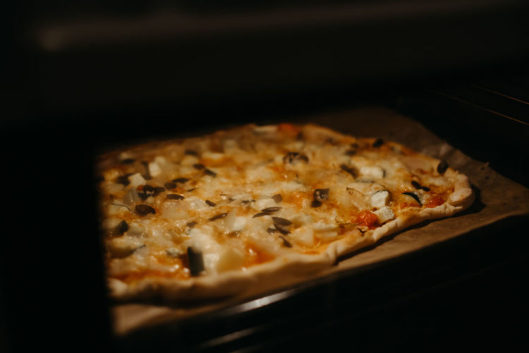 close-up of a homemade pizza in an oven Indoors  Food And Drink Food Nutrition Ingredient Ingredients Italia Italian Food Pizza Pizza Time Cheese Dairy Product Freshness Black Background Unhealthy Eating Oven Baked Olives Cheese! No People Baking Sheet Homemade Homemade Food Homemade Pizza