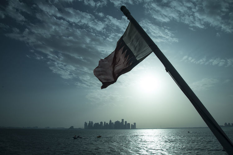 Low angle view of flag on sea against sky