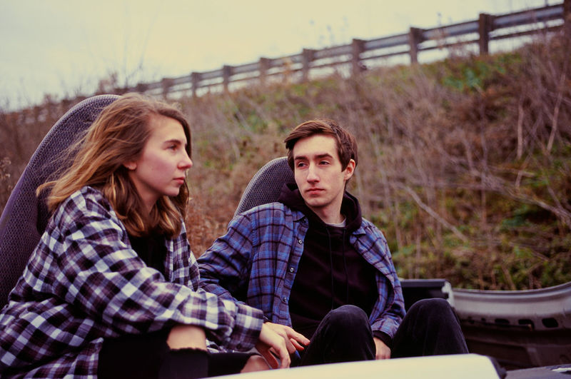 Young couple sitting in the remains of a car in an auto salvage yard