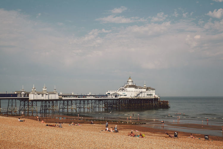 Eastbourne pier at beach against sky