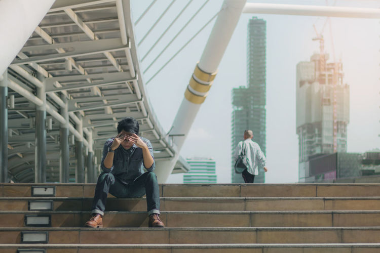 Stressed Man Sitting On Staircase Against Building