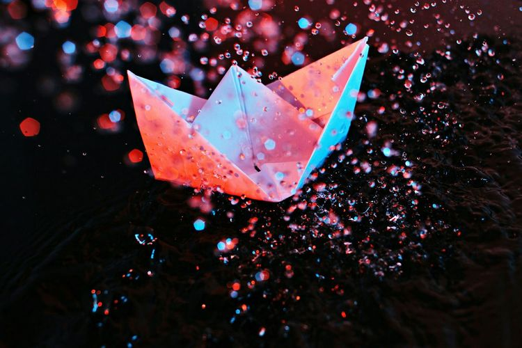 High angle view of paper boat and splashing water at pond