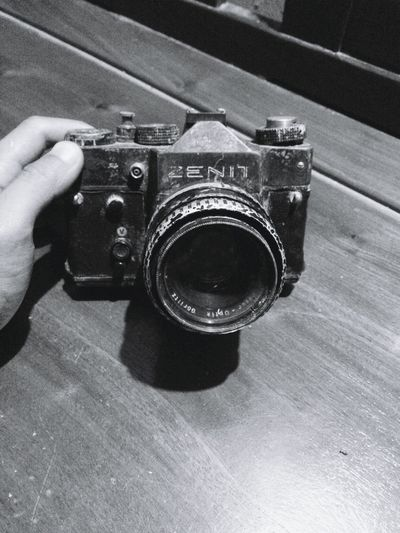 Close-up of hand holding camera on table
