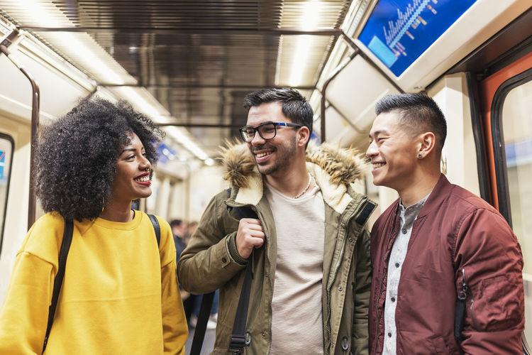Happy friends standing in train