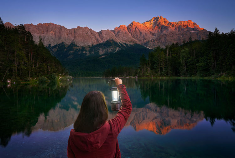 The Zugspitze is the highest mountain in Germany at 2,962 m above sea level. This photo was taken at the Eibsee Lake of my girlfriend holding a lamp. Alps Eibsee Europe Fantasy German Germany Girl Glow Highest Lake Lamp Landscape Mountain Mountains Natural Nature Outdoors Portrait Reflection Summer Sunset Tranquility Travel Woman Zugspitze The Portraitist - 2017 EyeEm Awards The Great Outdoors - 2017 EyeEm Awards