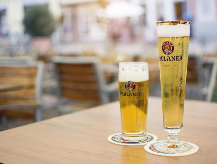 Two Glasses of Paulaner German Beer Drink Refreshment Glass Table Focus On Foreground Food And Drink Text Drinking Glass No People Wood - Material Household Equipment Beer - Alcohol Transparent Alcohol Beer Bar Pub Cold Cool Foam Beverage Brewery Liquid Freshness Bubles Scale  Cup