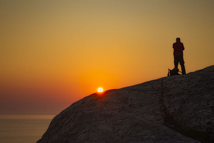 Man Standing On Cliff During Sunset