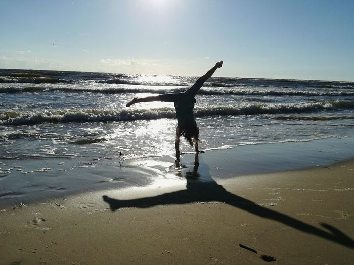 Silhouette woman doing handstand on wet shore
