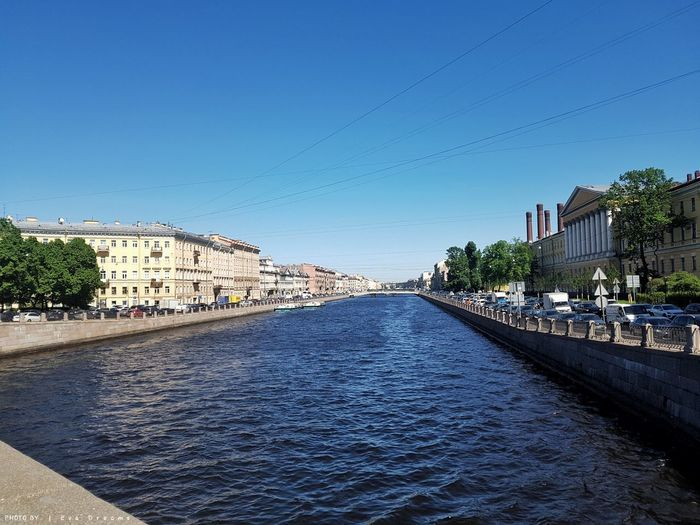 River amidst buildings against clear blue sky