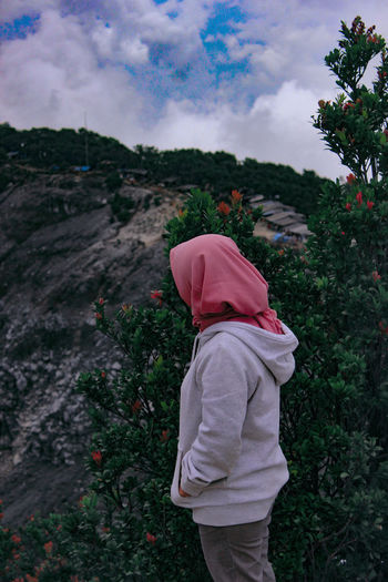 Side view of woman wearing hijab while standing by plants