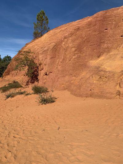 Rock formations on desert land against sky