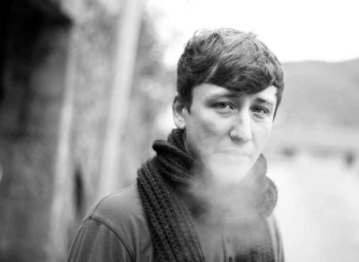 Close-up portrait of young man exhaling breath vapor
