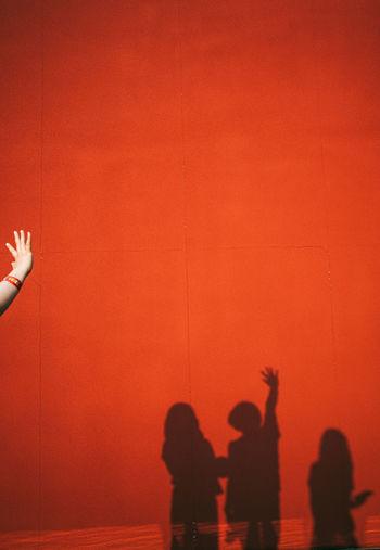 Silhouette people against orange wall