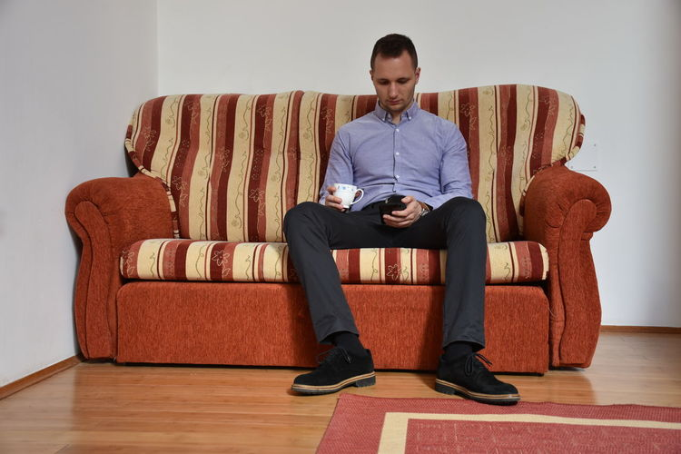 Full Length Of Man Using Phone While Sitting On Sofa At Home
