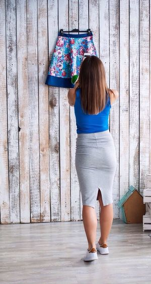 Rear view of fashion designer standing against skirt hanging on wall