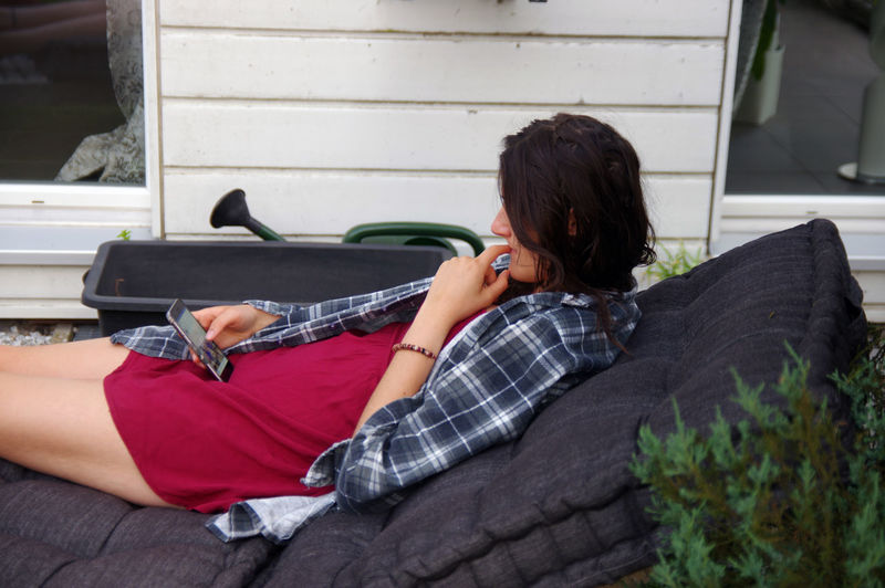 Young woman using phone on sofa