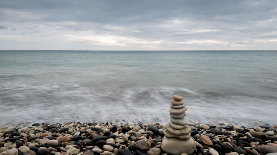 Scenic view of pebbles on beach against sky