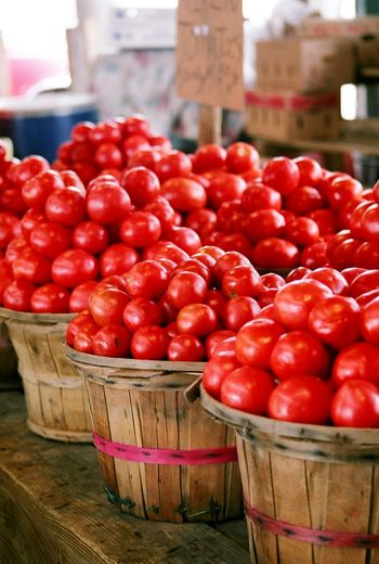 Fresh red organic tomatoes in wooden basket for sale