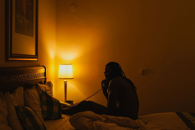 Light and Self. Bed Furniture Real People Bedroom Indoors  Lighting Equipment One Person Illuminated Domestic Room Electric Lamp Lifestyles Sitting Home Interior Rear View Technology Men Linen Orange Color Women