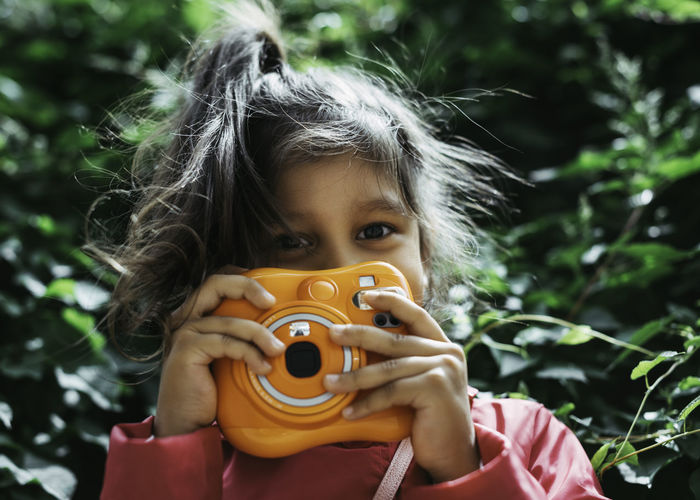 Portrait of cute girl holding camera