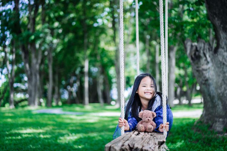 Portrait of smiling girl sitting on grass against trees