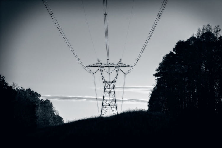 Transmission Tower in Black and White Electricity  Sky Tree Fuel And Power Generation Cable Power Supply Power Line  Silhouette No People Low Angle View Landscape Outdoors Electrical Component Land Transmission Line Transmission Tower