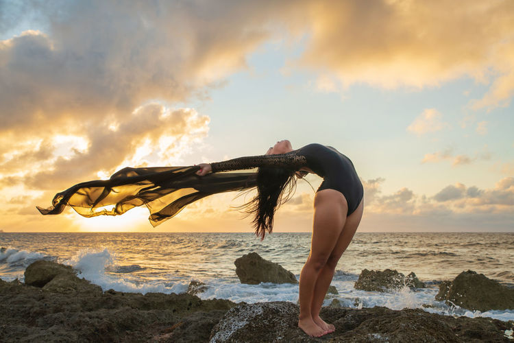 Young female dancer on beach against sky during sunset