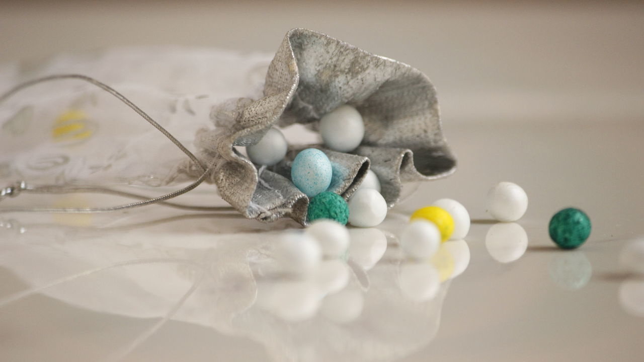 Close-Up Of Polystyrene Balls And Small Satchel On Floor