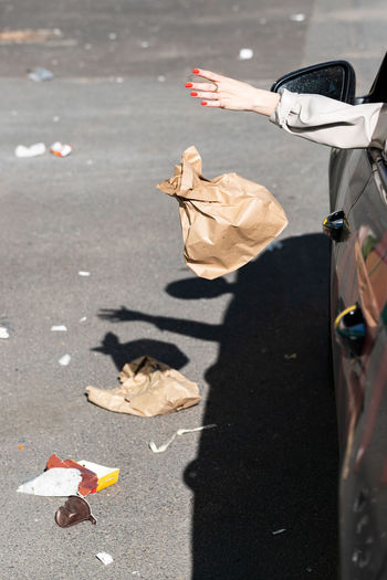 Cropped hand of woman throwing trash from car