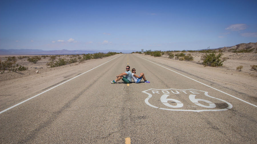 Side view of couple sitting on road against blue sky