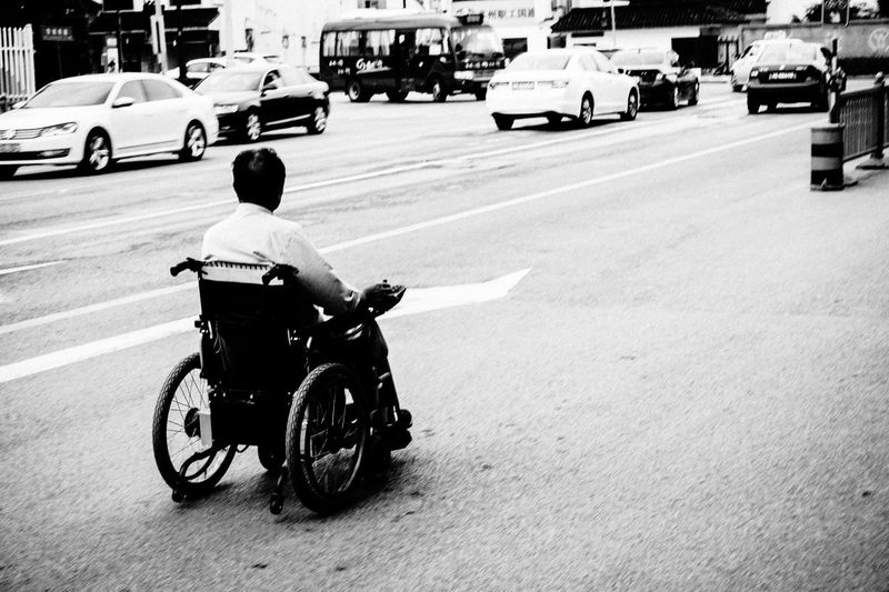 Man in wheelchair on road by cars at city