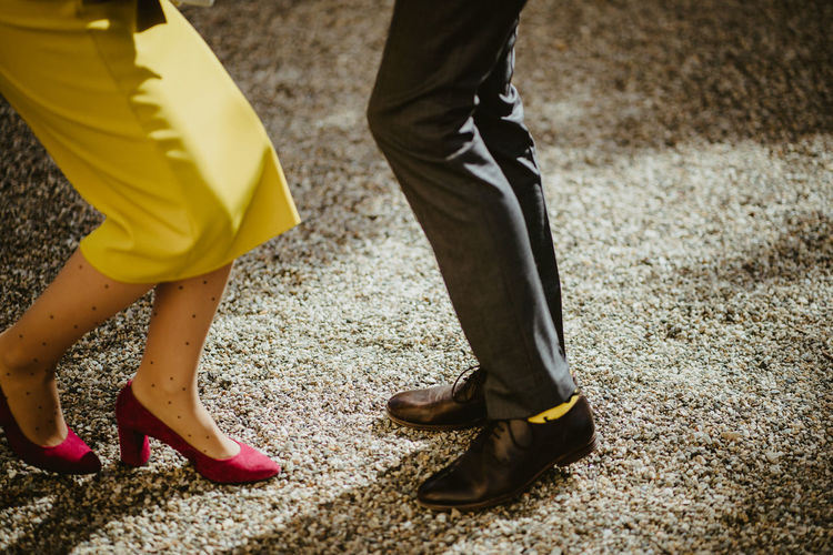 Low section of man and woman standing on yellow shoes