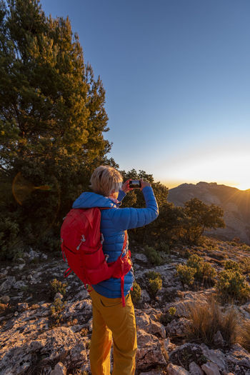 Rear view of person photographing on mountain against sky