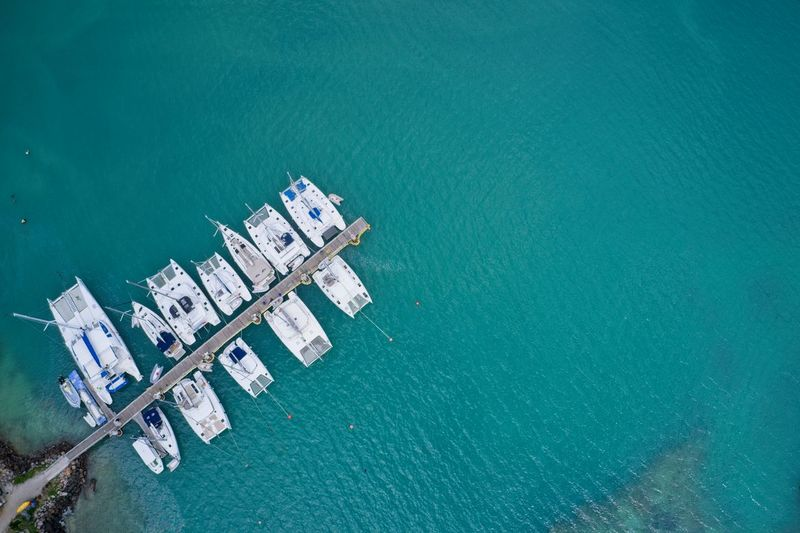 Drone field of view of boats moored in harbour in turquoise blue water praslin seychelles.