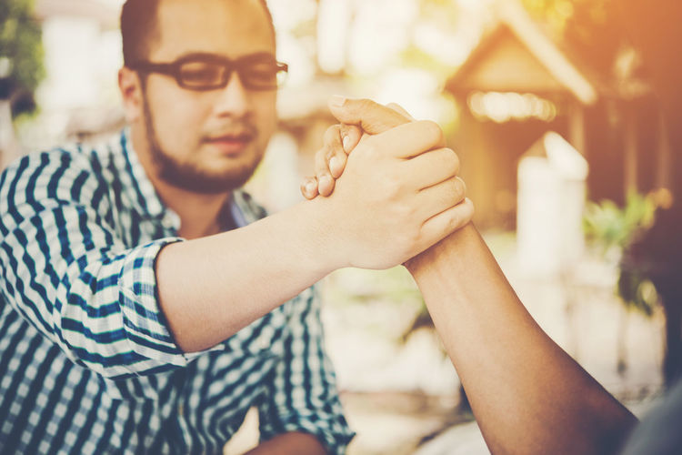 Close-Up Of Business Colleagues Holding Hands Outdoors
