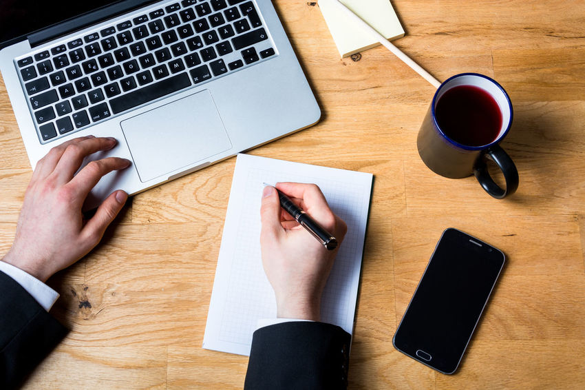 Taking business notes on work desk with laptop, smartphone and other accessories on wooden table. Wearing a white shirt and black jacket. Seen from above Arm Black Business Desk From Above  Hand Jacket Keyboard Laptop Light Mug NotePad Notes Office Shirt Smartphone Wooden Work Work Space