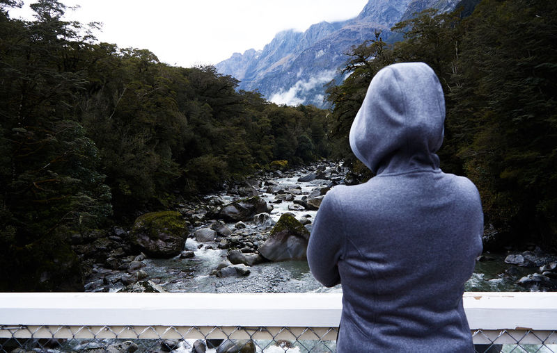Rear View Of Person Wearing Hooded Jacket Looking At Trees And River