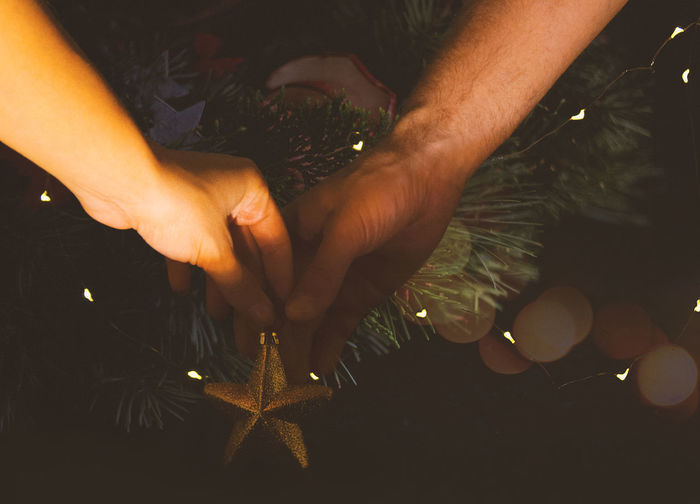 Cropped hands of people decorating christmas tree